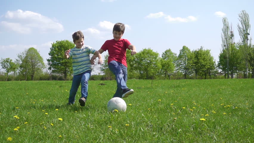 Two boys hit the ball on green play field with dandelions, slow motion 250 fps | Shutterstock HD Video #32809087