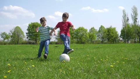 Two boys hit the ball on green play field with dandelions, slow motion 250 fps