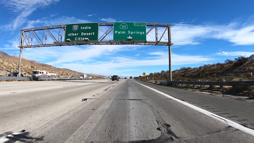 Slow motion driving view of Palm Springs Highway 111 exit sign on Interstate 10 in Southern California.