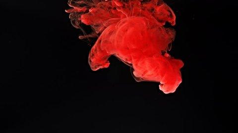 Red ink splash in water on black background