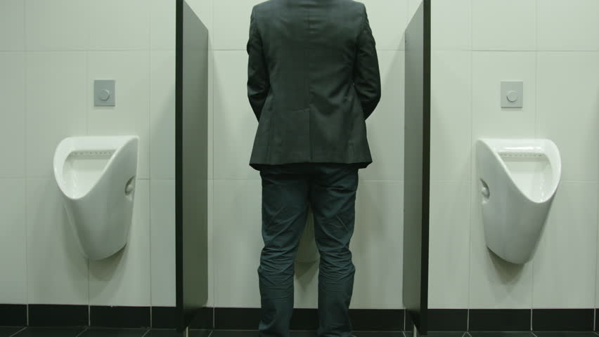 Man peeing to toilet bowl in restroom. Long shot
