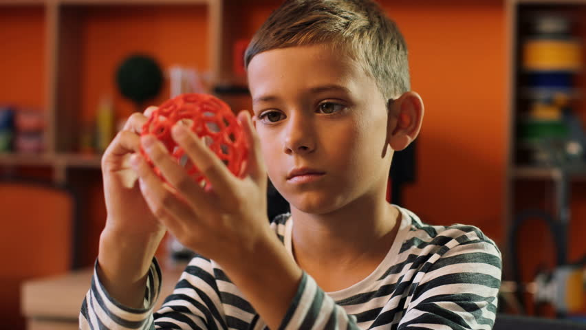 Close up of a cute boy holding a plastic red sphere and looking at it. 3D print. Indoor. Portrait shot