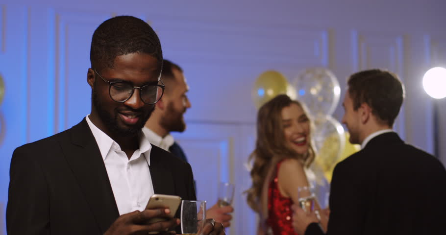 Attractive African American young man in glasses and suit taping on his smart phone, drinking Champagne and smiling at the glamorous party. Dancing people and balloons on the background. Indoor