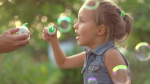Happy Mother and her little Daughter playing together outdoor, blowing soap bubbles, having fun on backyard. Nature. Beauty Mum and her Child in Park together. Family, Mother's Day Joy. Mom and Baby