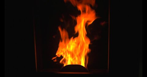 Flames burn in pellet stove heating houses with economical and renewable biomass