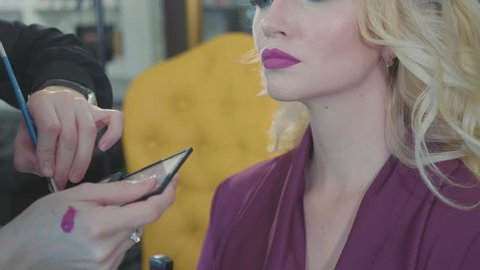 Close up of young girls's make-up process at beauty shop. Young visagiste applying pomade on model's lips. Blonde woman sitting while artist is correcting the shape of lips.