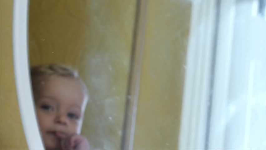 funny cute 9-10 months old baby boy looking in mirror