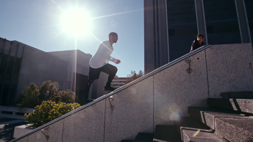 Free runners in action outdoors in city. Two young men doing parkour tricking and freerunning in the city. Jumping from an obstacle and running.