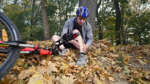 A young man sits in a park after falling from a bike, calms the pain in his knee, is a dangerous bike ride in the park on an autumn day