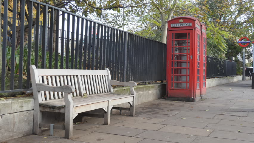 A bench and red telephone booths on the sidewalk. | Shutterstock HD Video #32926297