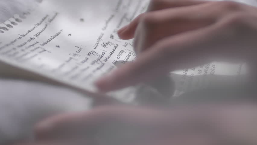 Close up of elegant hand of unrecognizable woman touching handwritten love letter while reading it
