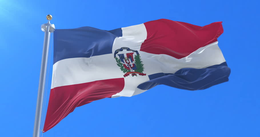 Flag of the Dominican Republic waving at wind with blue sky in slow, loop