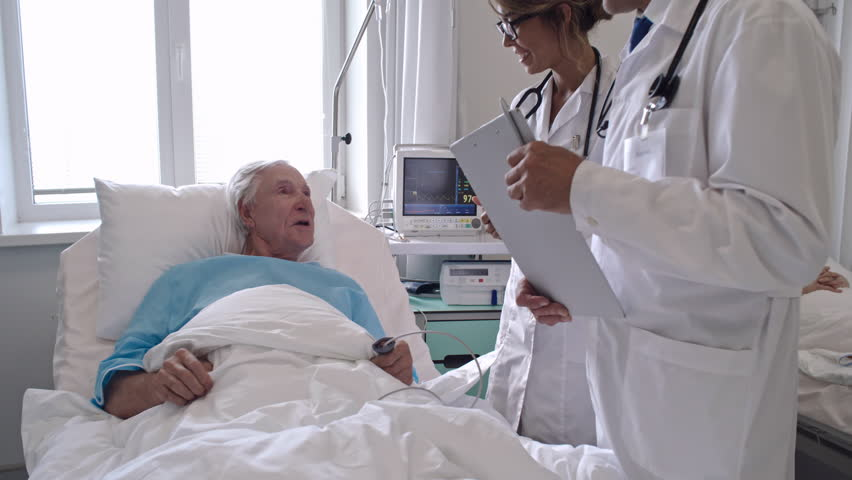 Zoom out of senior patient lying on hospital bed during medical exam and speaking with friendly healthcare workers | Shutterstock HD Video #32974267