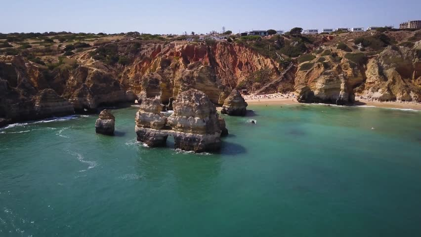 4k aerial drone footage - The famous Praia do Camilo beach.  Well known for it's rock formations and rugged cliffs.  Located in Lagos.  Algarve region of Portugal.
