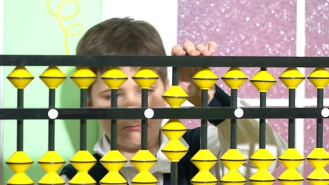 School boy dressed up as teacher holding abacus in a classroom.
