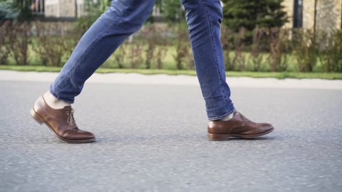 Unrecognizable man wearing blue jeans and brown leather shoes is walking in the street with no traffic. Side view. Tracking real time establishing shot