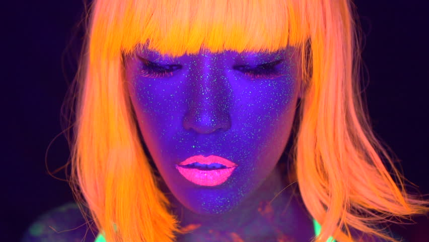 Closeup woman face with fluorescent make up in orange, wig, creative makeup look great for nightclubs. Halloween party, shows and music concept - slow motion video | Shutterstock HD Video #33046327