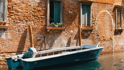VENICE, ITALY, SEPTEMBER 7, 2017: A motor boat stands on a Venetian canal under a beautiful vintage brick wall and windows with flowers in pots on the windowsills