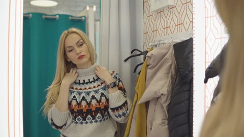 Beautiful woman measures the clothes in a fitting room.