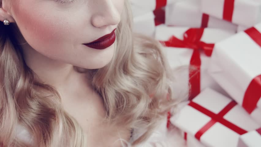 Pretty beautiful face of a young girl with bright makeup. Girl and gifts. Red lips. White gift boxes with red ribbons.     Shutterstock HD Video #33058099