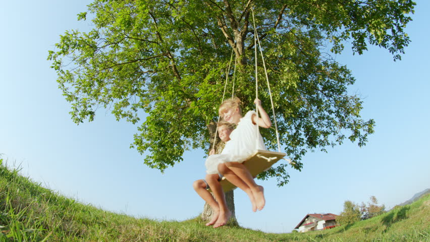 SLOW MOTION LOW ANGLE Playful young children enjoying swinging on a wooden swing under a big green tree. Smiling boy and girl swaying outdoors. Happy brother and sister on a swing set on a sunny day