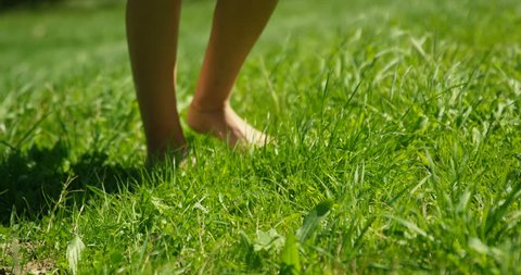 Close-up Shot of the Woman's Feet Walking on the Green Summer Grass. She Wears Stylish Dress and Holds Mobile Phone. Happy Summer Time. Shot on RED Epic 4K UHD Camera.