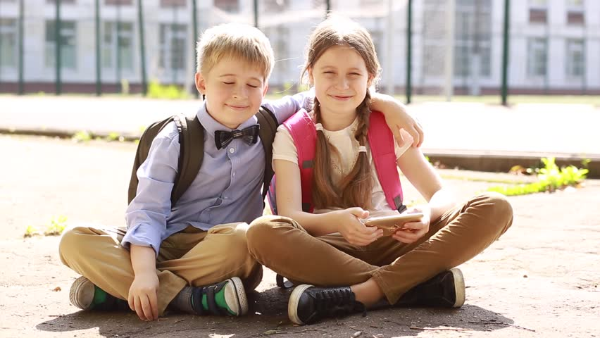 Boy and girl sharing together using smartphone.  Friends are sitting in front of the school  having fun using smart phone. Happy friendship lifestyle  | Shutterstock HD Video #33071398