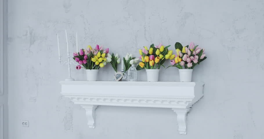 Beautiful studio celebratory background with bouquets of flowers and candles. Yellow, pink and purple tulips in vases on a shelf. | Shutterstock HD Video #33073627
