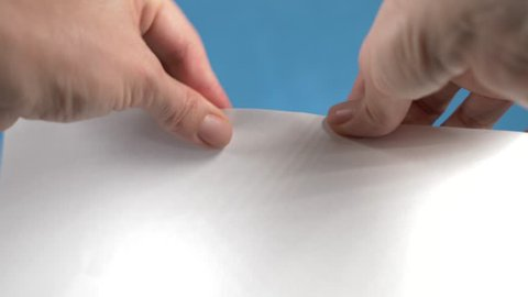 Hands tearing paper sheet, closeup on a turquoise background. 4k, slow motion
