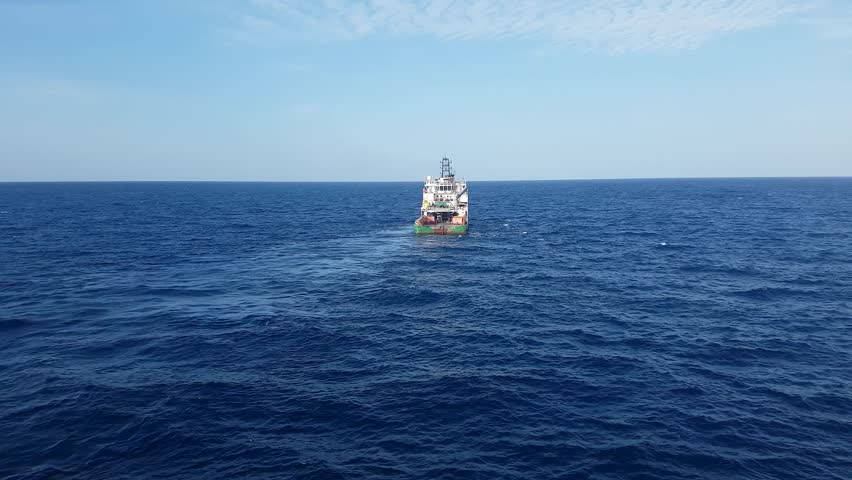 Supply boat pulling anchor for oil drilling rig in the middle of the ocean