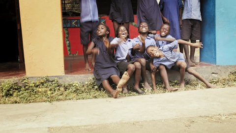 4k of African school pupils/ children smiling and waving for the camera.