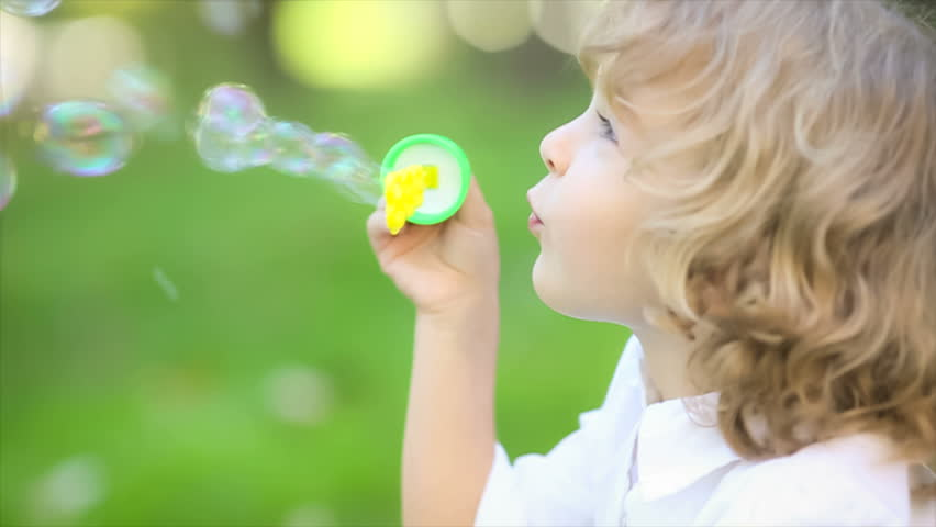 Happy child blowing soap bubbles in spring park. Slow motion | Shutterstock Video #3309644