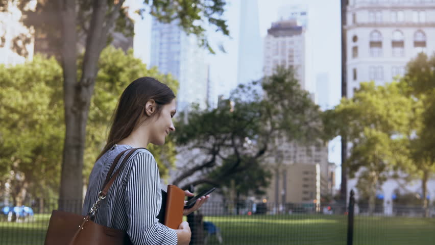 Young beautiful female walking through the park at work. Businesswoman holding the documents and using smartphone. | Shutterstock HD Video #33104992