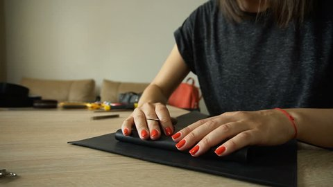 Slow motion female carefully preparing leather for making black purse. Young woman decided to start business and rented room for bags manufacturing. Craftswoman with red manicure and bracelet wearing