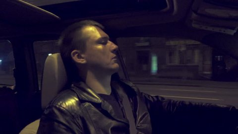 Tired sleepy man drives the car through the night city