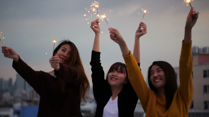 Outdoor shot of young people at rooftop party. Happy group of asia girl friends enjoy and play sparkler at roof top party at evening sunset. Holiday celebration festive party. Teenage lifestyle party.