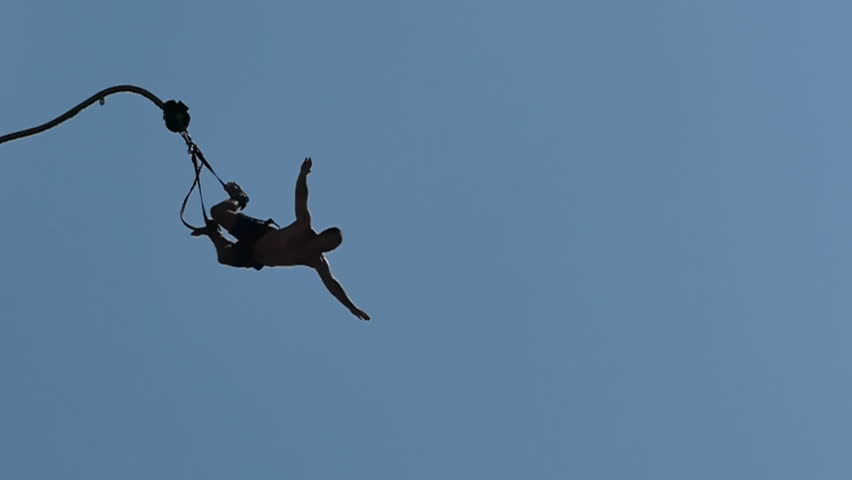 Man is jumping from the top of a Bungee Jumping ; Exhilarating bungee jump from the high platform above sea level, slow motion video clip