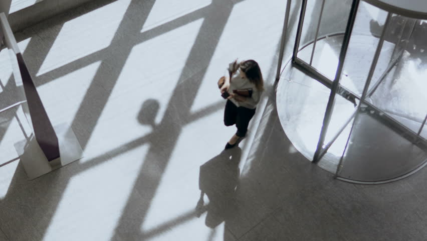 Top view of businesswoman or female manager coming to work in office, going through revolving door and use smartphone.
