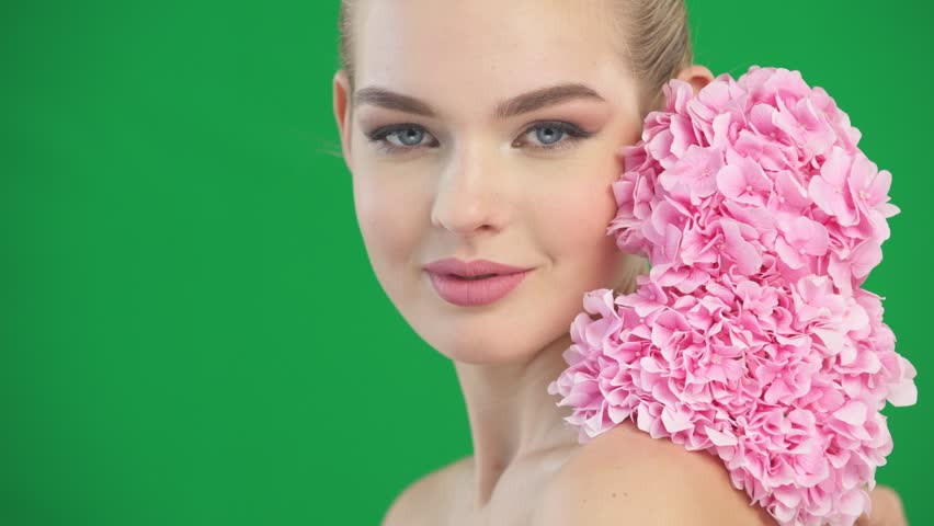 Closeup portrait of young beautiful woman with a healthy clean skin of the face. Pretty adult girl with flower near the face.  - isolated on white background. | Shutterstock HD Video #33144667