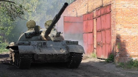 Military tank driving on road slow motion. War tank driving on dirty road on bakground brick building
