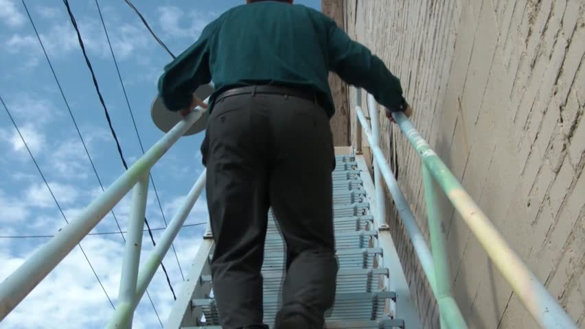 Businessman walks up shaky metal stairs in downtown urban setting with wires and blue sky in background.