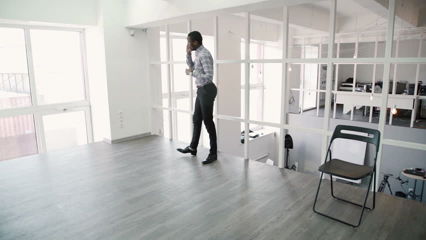 Young man is talking on phone, walking around modern office. | Shutterstock HD Video #33159607
