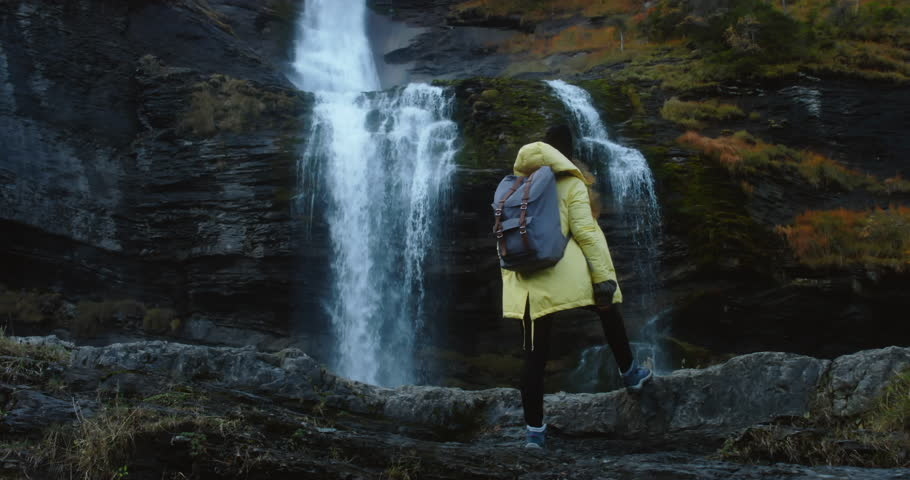 CINEMAGRAPH - SEAMLESS LOOP. Caucasian female hiker in yellow raincoat enjoys the view of a beautiful waterfall in French Alps
