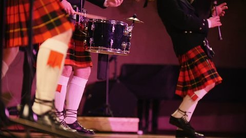 Traditional scottish band musicians in white socks and kilts singing with bagpipes on the stage