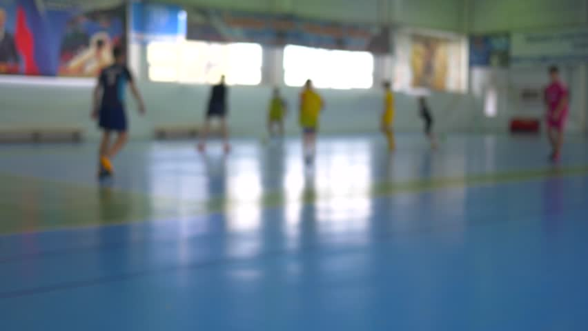 Football futsal training for children. Indoor soccer young player with a soccer ball in a sports hall.