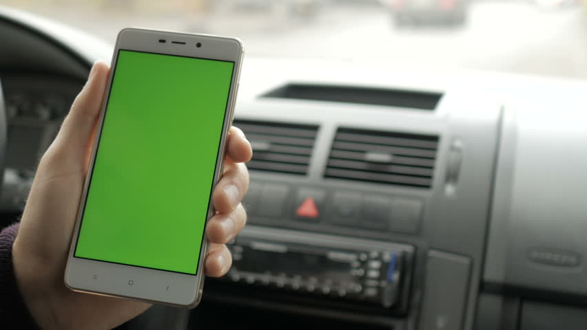 A hand holding a smartphone with green blank screen in the car for direction, massage, location, business. Man sits in modern car and works on smartphone - green screen - closeup. Chroma key.