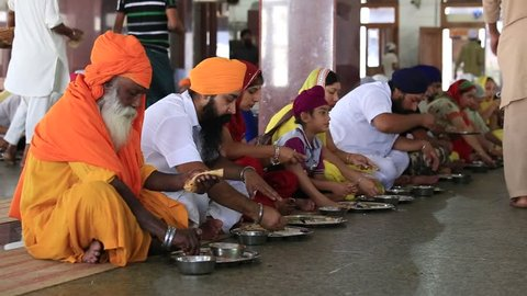 AMRITSAR, INDIA - SEPTEMBER 27, 2014: Unidentified poor indian people receive a free meal inside the 'langar', a communal kitchen on the famous Sikh Golden Temple complex in Amritsar.
