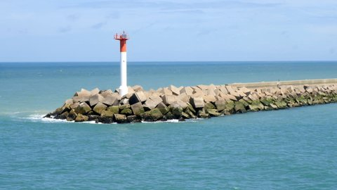 Breakwater or jetty with beacon sea mark powered by solar panel at the entrance to the port of Dunkirk, France