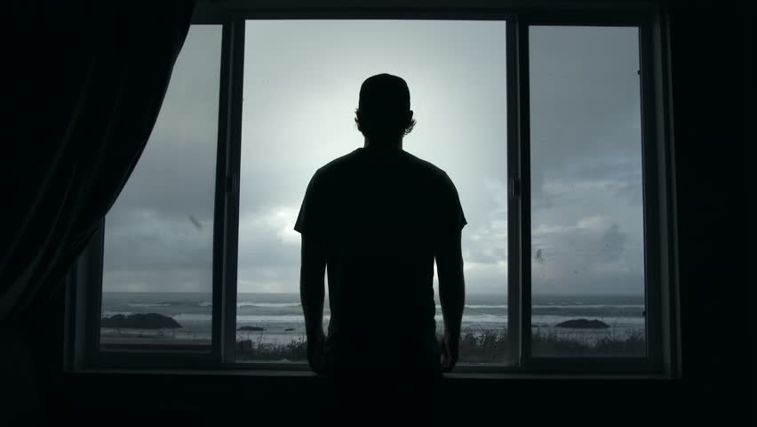 Man looks through picture window out at the ocean during stormy day on the Oregon Coast with seabirds flying by.