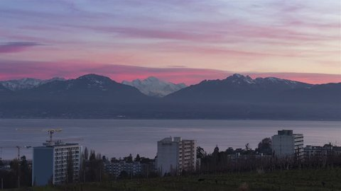 Mont-Blanc, the bigest mountaine of Europa in front of Geneva lake at purple pink and red sunset - city of Morges - Switzerland France Timelapse 4K